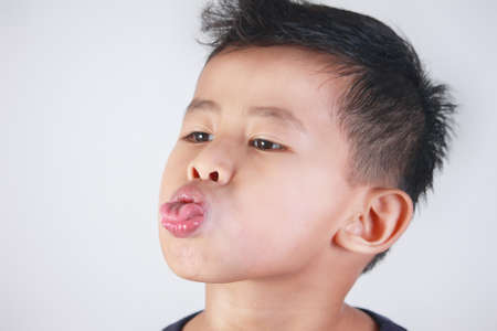 Portrait of young Asian boy sticking out his tongue mocking gesture Stockfoto