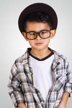 cool kids: Portrait of cute happy young Asian boy wearing hat and glasses smiling