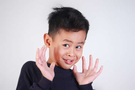mocking: closeup portrait of young Asian boy being shocked of something and mocking gesture Stock Photo