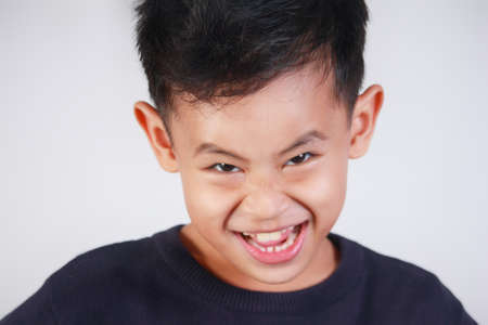 Portrait of young Asian boy with naughty evil grin smile
