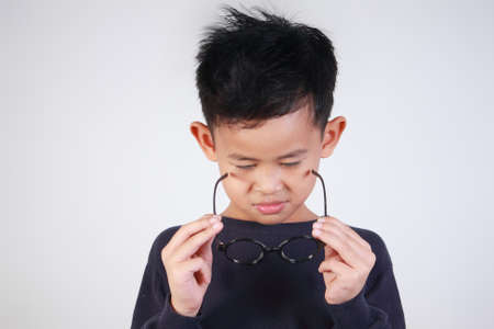 Portrait of little Asian boy wearing his glasses on Stock Photo