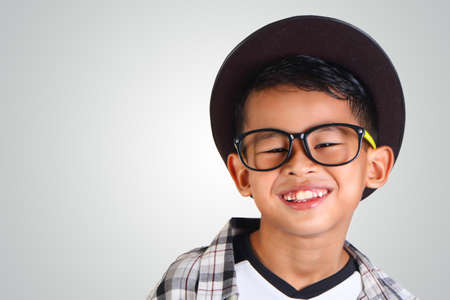 fashion boy: Portrait of cute happy young Asian boy wearing hat and glasses smiling