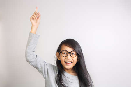 asian children: Portrait of beautiful little Asian student girl smiling enthusiastic and raise her hand and pointing finger up to get attention from teacher in class