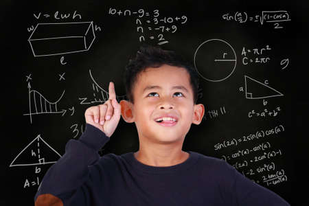 equivalent: Portrait of little Asian student boy smiling and raise his pointing finger up, get an idea to solve math problem, over blackboard with mathematic schemes doodle drawn on it