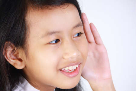 secretly: closeup portrait of beautiful little Asian girl listening carefully with her hand to ear gesture trying to hear secretly interesting information conversation news