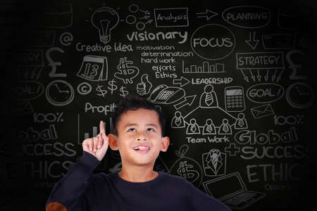 Portrait of little Asian student boy smiling and raise his pointing finger up, get an idea gesture, over blackboard with business scheme doodle drawn on it