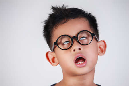 Portrét asijského chlapce s brýlemi ukazuje velmi líné nešťastné nudné a unavené gesto Reklamní fotografie