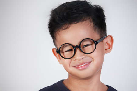 Portrait of little Asian boy wearing glasses smiling happily Stock Photo