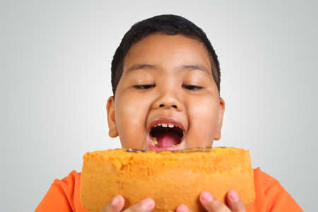 Portrait of a fat Asian boy eating big piece of cake Zdjęcie Seryjne