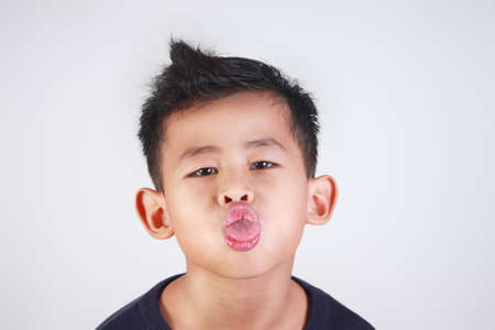 mocking: Portrait of young Asian boy sticking out his tongue mocking gesture Stock Photo