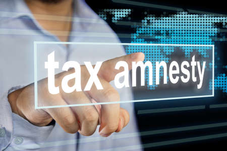 Businessman clicking Tax Amnesty words on virtual screen