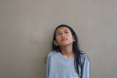 girl looking up: Little Asian girl standing against grey wall, looking to the sky and thinking something Stock Photo