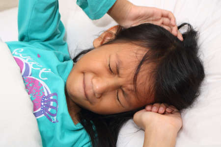 Little Asian girl having nightmare while sleeping Archivio Fotografico
