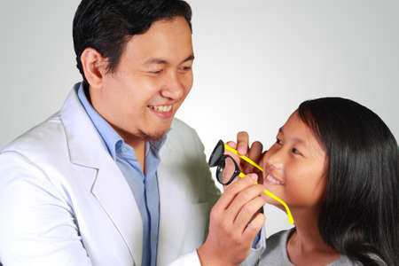 myopia: Photo image of a young Asian male Ophthalmologist, eye doctor giving eyeglasses to a happy young patient girl Stock Photo