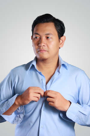 cuff link: Photo image of a handsome attractive young Asian businessman dressing, buttoning his blue shirt. Wedding preparation. Ready to work in formal wear