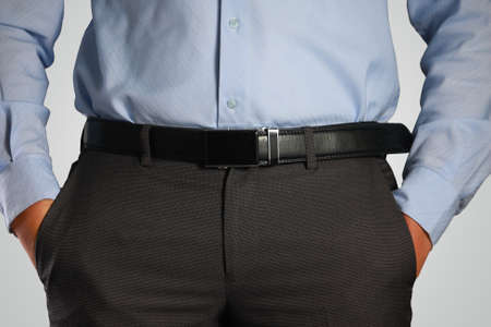 body torso: Photo image closeup shot of male waist with hands in pocket dressed in black pants, belt, blue shirt. Formal wear Stock Photo
