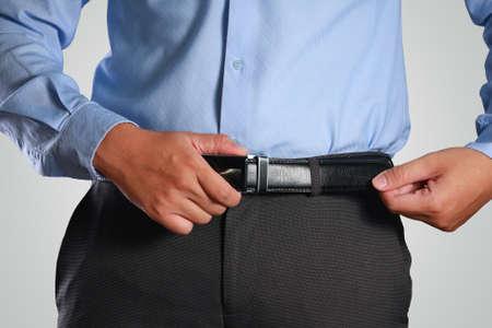Foto Bild eines Unternehmers, seinen Gürtel Konzept für eine Rezession oder wirtschaftliche Depression Anziehen Standard-Bild - 65511662
