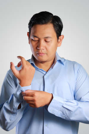cuff link: Photo image of a handsome attractive young Asian businessman dressing, button up his shirt sleeve. Wedding preparation. Ready to work in formal wear Stock Photo