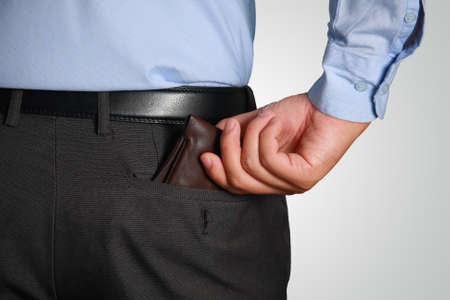 hand in pocket: Photo image of a businessman picking up his wallet from his pocket, rear view
