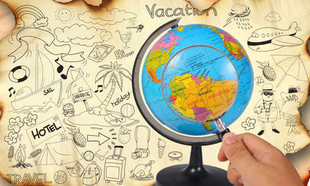 hand holding paper: Photo image of a hand holding magnifying glass looking on earth globe, planning for vacation travel trip destination concept, on old grunge paper with travelling doodle illustration