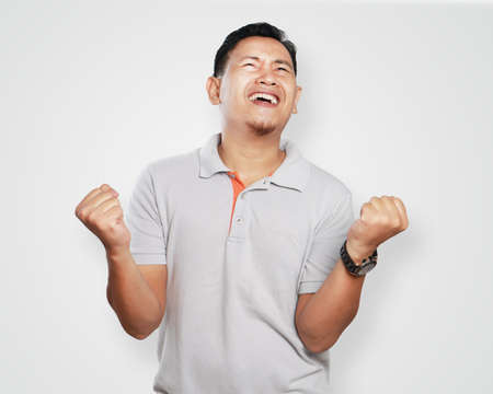 success man: Photo image portrait of a cute handsome young Asian man screaming celebrating victory, successful winning gesture