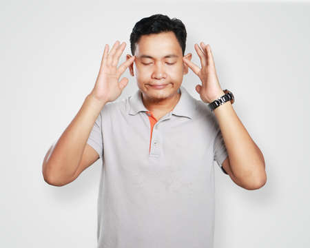 anger management: Photo image portrait of a cute young Asian man doing meditation with eyes closed and touching his forehead with his finger