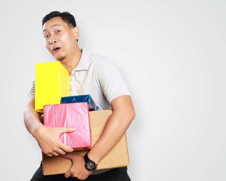 Photo image portrait of a cute handsome young Asian courier man smiling happily while holding lots of gift box package