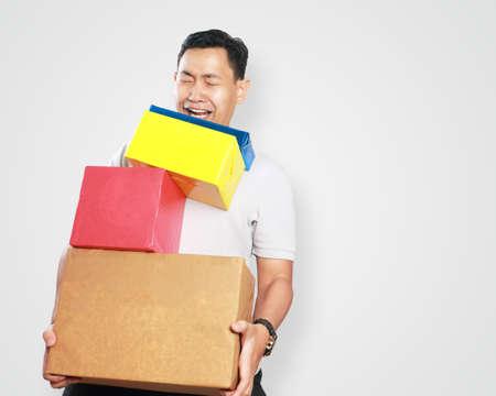 caras felices: retrato de la imagen de la foto de un apuesto joven linda asiática mensajería sonriendo feliz en posesión de una gran cantidad de paquete de la caja de regalo