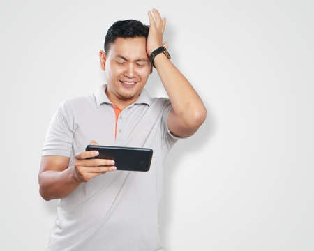 games hand: Photo image portrait of a cute handsome young Asian man with funny face playing games on tablet, loosing gesture, hit his forehead with left hand