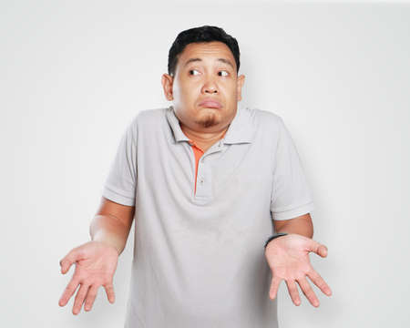 Photo image portrait of a cute young Asian man showing I dont know gesture, shoulder shrug and looking to the side