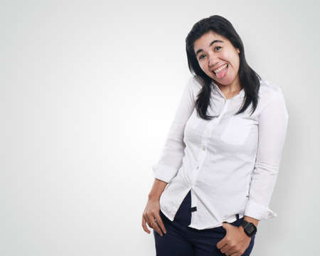 looked: Photo image portrait of a beautiful cute young Asian businesswoman looked very excited and happy, funny face smiling, tongue out with both hands on her waist, half body close up portrait