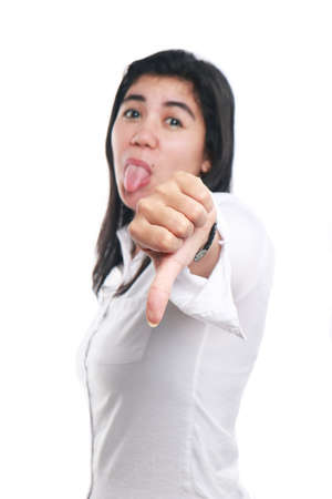 mocking: Photo image portrait of a beautiful cute young Asian woman showing thumb down gesture with tongue out mocking face, side view half body close up portrait over white, focus on hand with blur face Stock Photo
