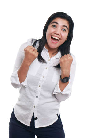 Photo image portrait of a successful cute young Asian businesswoman looked excited, smiling and showing winning gesture, half body close up portrait over white background Фото со стока
