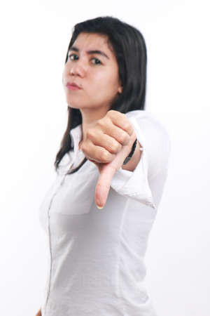 disapprove: Photo image portrait of a beautiful cute young Asian woman showing thumb down gesture with angry face, side view half body close up portrait over white, focus on hand with blur face