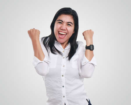 looked: Photo image portrait of a successful cute young Asian businesswoman looked excited, smiling and showing winning gesture, half body close up portrait
