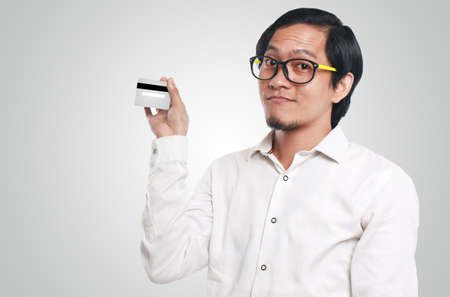 Photo image portrait of a funny young Asian businessman smiling while showing a credit card that he hold, close up portrait, commerce or consumer concept