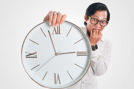 Photo image portrait of a funny young Asian businessman looked shocked and worried while showing a clock that he hold, close up portrait, time or deadline concept