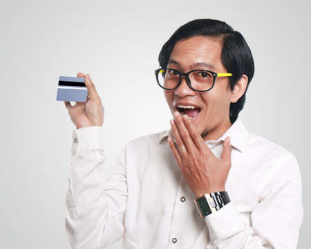 Photo image portrait of a funny young Asian businessman looked happy and smiling while showing a credit card that he hold, close up portrait, commerce or consumer concept