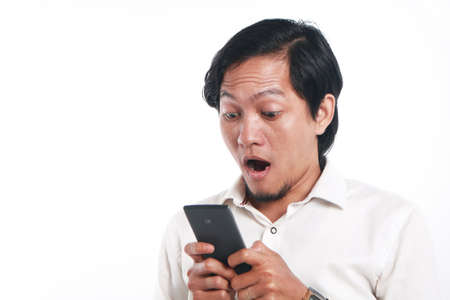 funny face: Photo image portrait of a funny young Asian man shocked while looking his smart phone. Holding phone with both hands while reading message on it, over white background Stock Photo