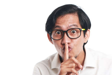 noiseless: Photo image portrait of a funny young Asian businessman wearing glasses showing ssh sign, close up portrait with one finger on lips asking to silence gesture, over white background