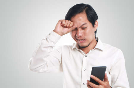 young man portrait: Photo image portrait of a funny young Asian man shocked while looking bad news on his smart phone. Hitting head with one hand, hold phone with other hand, failure concept