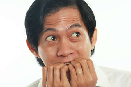 Photo image portrait of a funny young Asian businessman looked very scared and worried, close up portrait, biting nails gesture over white background