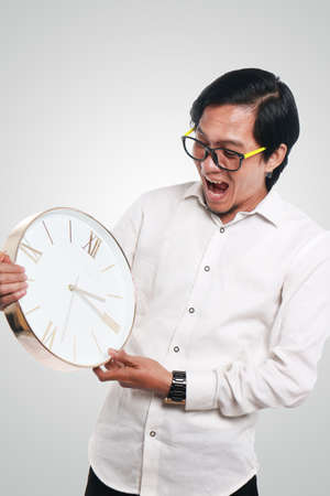 Photo image portrait of a funny young Asian businessman looked shocked while looking a clock that he hold, close up portrait, time or deadline concept