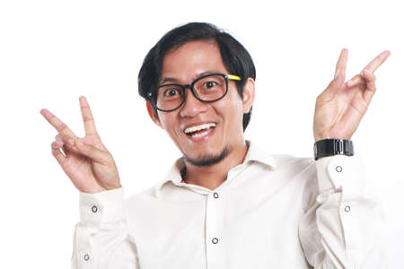 one people: Photo image portrait of a funny young Asian businessman wearing glasses looked very happy, close up portrait, big smile with both hand showing peace sign, victory gesture, over white background