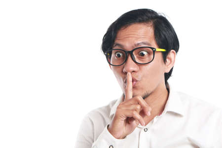 Photo image portrait of a funny young Asian businessman wearing glasses showing ssh sign, close up portrait with one finger on lips asking to silence gesture, over white background