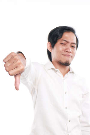 mocking: Photo image portrait of a cute funny young Asian man showing thumb down gesture with mocking face, close up portrait over white background