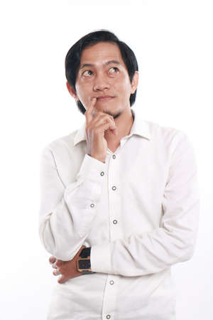 looked: Photo image portrait of a funny young Asian businessman looked happy and smiling while thinking of something, close up portrait with one hand touching his chin, over white background