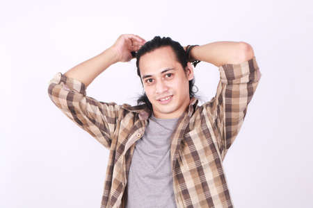 bundling: Photo image portrait of a cute young Asian male model smiling while tying his long hair