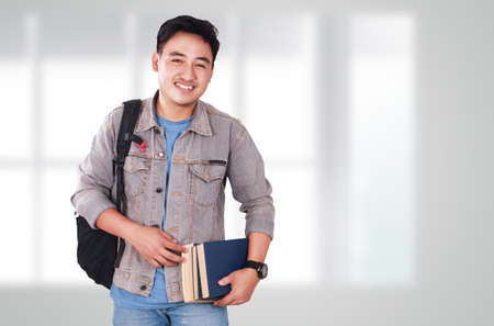 Photo image portrait of a cute young Asian male student standing, looking at camera and smiling while holding some books Stock Photo
