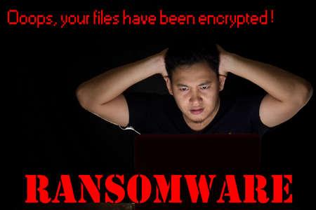 Jonge man geschokt voor zijn laptop in het donker om zijn bestanden op zijn computer te zien zijn gecodeerd door ransomware virus Stockfoto